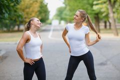 Beautiful, sexy sports girls exercising on a park background. Fitness lifestyle concept. Copy space. Royalty Free Stock Photo