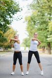 Beautiful, sexy sports girls exercising on a park background. Fitness lifestyle concept. Copy space. Stock Photo