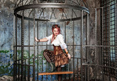 Beautiful sexy steampunk woman in the cage Royalty Free Stock Photography