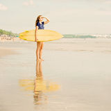 Beautiful sexy surfer girl on the beach at sunset Royalty Free Stock Photo