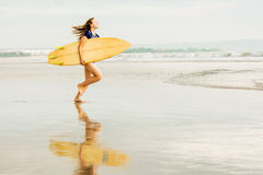 Beautiful sexy surfer girl on the beach at sunset Royalty Free Stock Image