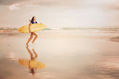 Beautiful sexy surfer girl on the beach at sunset Royalty Free Stock Photos