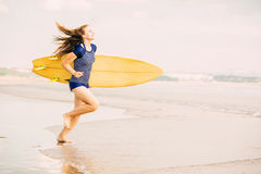 Beautiful sexy surfer girl on the beach at sunset Stock Photography