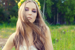 Beautiful sexy sweet girl with long hair and a wreath of yellow roses on his head in the field, the wind blowing her hair Royalty Free Stock Photo