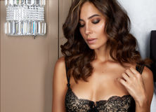 Beautiful sexy tanned brunette woman with curly hair in black lace lingerie with a beautiful evening makeup stands near a wall sco Royalty Free Stock Image