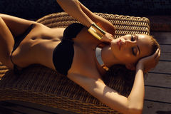 Beautiful sexy tanned girl with blond hair in elegant bikini. Fashion outdoor photo of beautiful sexy girl with blond hair in elegant bikini relaxing beside a Stock Photography