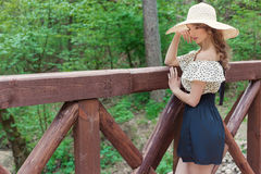 Beautiful sexy tender attractive woman with bare shoulders in a hat standing on a wooden bridge Royalty Free Stock Photo