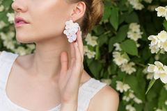 Beautiful sexy tender girl near blossoming tree exhibits beautiful delicate earrings in the form of flowers with rhinestones Royalty Free Stock Image
