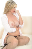 Beautiful Sexy Topless Young Woman Relaxing on a Sofa in an Open Shirt Stock Photography