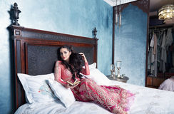 Beautiful sexy woman bed harem bedroom dress clothes fashion Royalty Free Stock Image