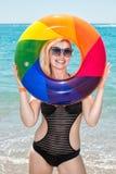 Beautiful woman in bikini with inflatable circle resting on the beach. stock image