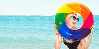 Beautiful woman in bikini with inflatable circle resting on the beach. royalty free stock photography