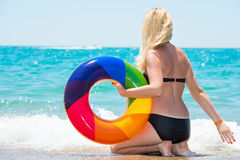 Beautiful sexy woman in bikini with inflatable circle sitting on the beach. Sexy woman in bikini with inflatable circle sitting on the beach Stock Image
