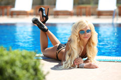 Beautiful sexy woman bikini model in fashion sunglasses tanned a. Nd lying by the blue swimming pool, summer vacation. Resort. Healthy body care Stock Photos