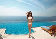 Beautiful sexy woman bikini model with long healthy hair, brunet. Te posing and tanned by the blue swimming pool, summer vacation. Fit body. Healthy body care Stock Images