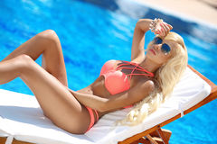 Beautiful sexy woman bikini model tanned and lying on deck chair. By the blue swimming pool,summer vacation. Resort. Healthy body care Stock Photography