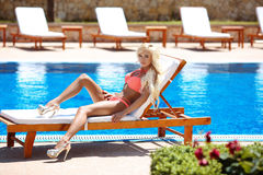 Beautiful sexy woman bikini model tanned and lying on deck chair Royalty Free Stock Image