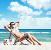Beautiful sexy woman in bikini relaxing on the beach. Attractive young girl in bikini sunbathing on beach. Traveling, holiday, vacation concept Stock Image