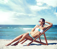 Beautiful sexy woman in bikini relaxing on the beach. Beautiful and sexy woman in bikini relaxing on beach. Traveling, holiday, vacation concept Royalty Free Stock Photography