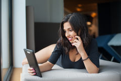 Beautiful sexy woman in black bodysuit lying on mattress and looking at tablet computer at luxury resort Stock Photography