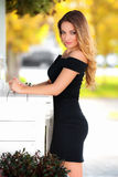 Beautiful sexy woman with black dress and blond hair posing outdoor. Fashion girl Royalty Free Stock Photo
