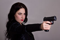 Beautiful sexy woman in black with gun over grey Royalty Free Stock Images