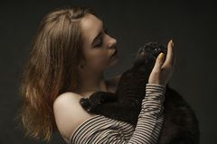 Beautiful sexy woman in black holding black cat. Beautiful young and stylish woman holding a gray cat. Studio photo. art stock images