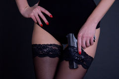 Beautiful sexy woman in black lingerie with gun over grey Royalty Free Stock Photo
