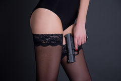 Beautiful sexy woman in black lingerie holding gun over grey Stock Image