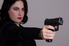 Beautiful sexy woman in black shooting with gun over grey Royalty Free Stock Photography