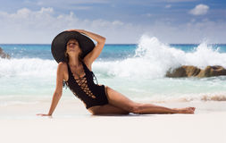 Beautiful, sexy woman in black swimming dress and straw sunhat Royalty Free Stock Photography
