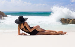 Beautiful, sexy woman in black swimming dress and straw sunhat Stock Photos
