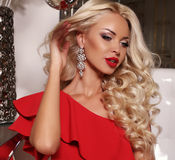 Beautiful woman with blond hair in luxurious red dress and bijou. Fashion interior photo of beautiful woman with blond hair in luxurious red dress and bijou stock images