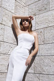 Beautiful woman blond hair model fashion style dress wear. White color dress sun shine shadow wall tanned skin summer weather vogue glamour lady body face stock photos