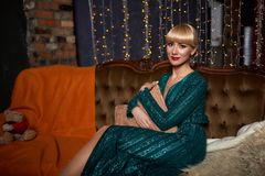 Beautiful woman blonde in elegant green sparkling dress. Fashion model with long legs posing in dark interior. royalty free stock images