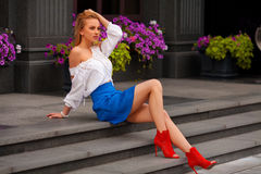 Beautiful sexy woman with blue skirt and blond hair posing outdoor. Fashion girl in red shoes Royalty Free Stock Photo