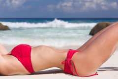 Beautiful and sexy woman body torso in red swimsuit, at tropical sandy beach Stock Photography