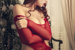 Beautiful sexy woman body in transperent clothes, red lipstick and curly hair. New year. Unrecognizable, faceless Royalty Free Stock Photo