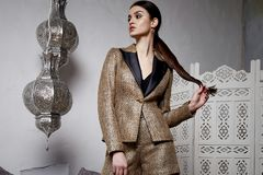 Beautiful sexy woman brunette hair east arabic morocco. Furniture glamour model pose fashion clothes skinny wool gold short jacket business style accessory hand Stock Photography