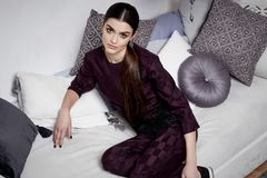 Beautiful sexy woman brunette hair east style arabic morocco. Furniture glamour model pose fashion clothes skinny silk cotton suit trousers blouse accessory Royalty Free Stock Photography