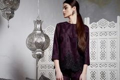 Beautiful sexy woman brunette hair east style arabic morocco. Furniture glamour model pose fashion clothes skinny silk cotton suit trousers blouse accessory Stock Image
