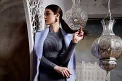 Beautiful sexy woman brunette hair east style arabic morocco. Furniture glamour model pose fashion clothes skinny wool cotton dress coat jacket accessory hand Royalty Free Stock Photos