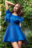 Beautiful woman brunette model in a short blue silk fashionable stylish dress long beautiful tanned legs in high heels on a b. Ackground of green foliage of stock image