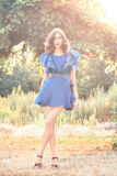 Beautiful woman brunette model in a short blue silk fashionable stylish dress long beautiful tanned legs in high heels on a b Royalty Free Stock Photography
