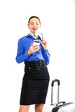Beautiful sexy woman in a business suit stands next to a suitcase and talking on the phone Royalty Free Stock Photos