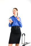 Beautiful sexy woman in a business suit stands next to a suitcase and talking on the phone Stock Images