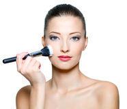 Beautiful woman doing make-up on face. With cosmetic brush - isolated on white royalty free stock image