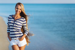 Beautiful sexy woman is dressed in a sea stripped vest sits on the seashore dreams Stock Photography