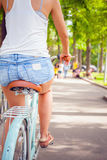 Beautiful sexy woman dressed in shorts travel by bicycle Stock Image