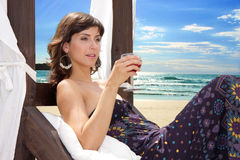 Beautiful sexy woman drinking and enjoying the sun on the beach. Beautiful brunette woman enjoying the sun and having a  drink on a beach bed Stock Photos